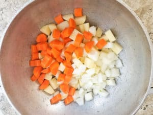 Chopped carrots, cubed potatoes, onions and garlic in a dutch oven cooking for the soup.