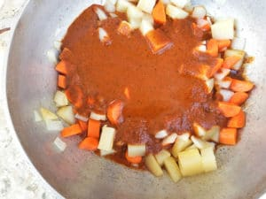 Tomato guajillo puree topped on the chopped carrots, cubed potatoes, onions and garlic in a dutch oven cooking for the Caldo de Camaron soup.