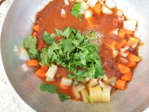 Chopped cilantro, oregano, chopped carrots, cubed potatoes, onions and garlic in a dutch oven cooking for the soup.