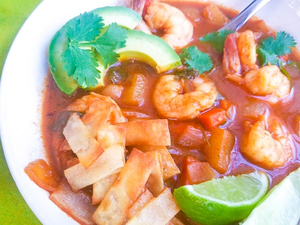 Caldo de Camaron (Mexican Shrimp Soup) served in a white bowl with tortilla strips, avocado slices and lime wedges.
