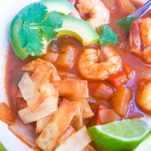 Caldo de Camaron (Mexican Shrimp Soup) served in a white bowl with tortilla strips, avocado slices and lime wedges.