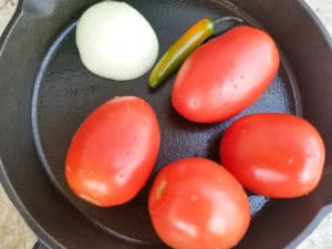 Tomatoes, half an onion and serrano pepper in a skillet to roast for the soup.