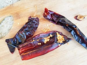Stems and seeds removed from guajillo peppers. Peppers are on a wooden cutting board.