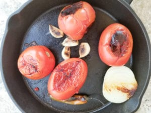 Tomatoes, half an onion, serrano pepper and garlic in a skillet fully roasted for the soup.