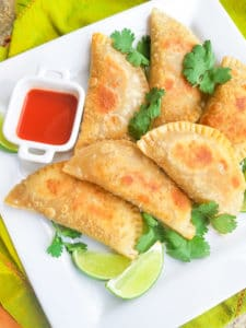 Empanadillas de Carne (Puerto Rican Empanadas) on a white platter with a side of hot sauce.