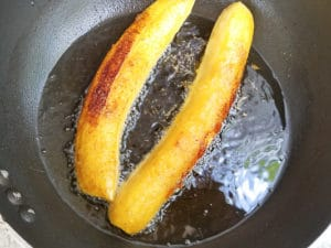 Ripe plantains being fried in a black skillet for the canoas.