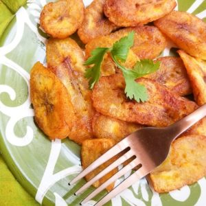 Platanos Fritos (Puerto Rican Sweet Plantains) on a green and white plate.