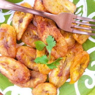 Platanos Fritos (Puerto Rican Sweet Plantains) cooked and serve on a green and white plate.