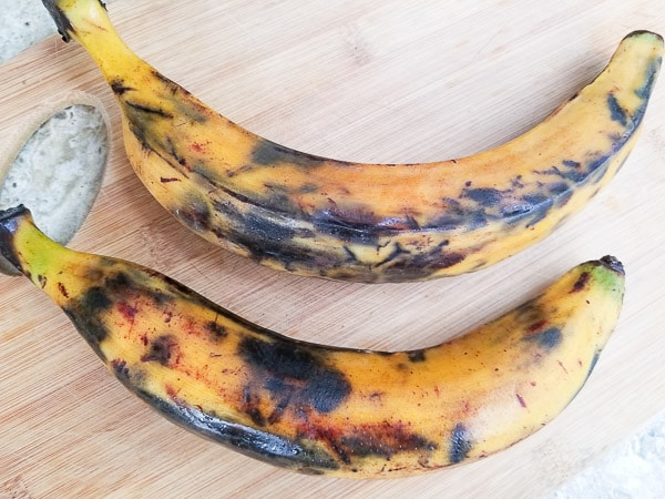Two ripe plantains on wooden cutting board.