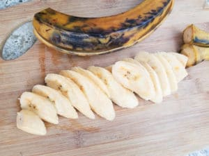 Plantains slices on a wooden cutting board for the platanos fritos (Puerto Rican Sweet Plantains).