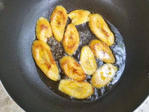 Cooking plantains slices in a skillet over medium heat until golden brown.
