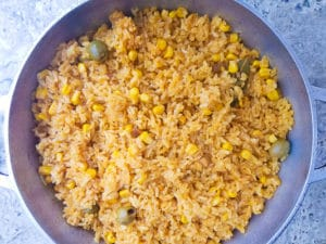Cooked Puerto Rican yellow rice with corn in a caldero-dutch pot.
