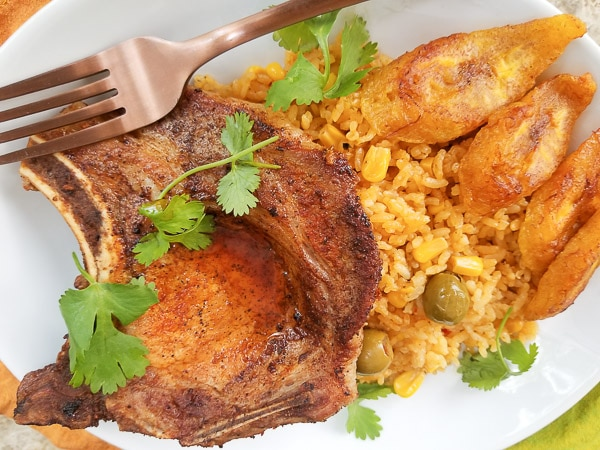 Baked pork chop with Puerto Rican yellow rice with corn and fried plantains served on a white plate.