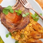 Puerto Rican Yellow Rice with Corn served in a large white platter with a fried pork chop and ripe fried plantains.