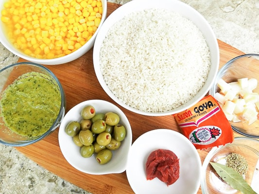Ingredients to make Puerto Rican Yellow Rice with orn on a wooden cutting board in individual bowls. Rice, corn, pork fat, sofrito, tomato paste, olives, bay leaf, oregano and sazon.