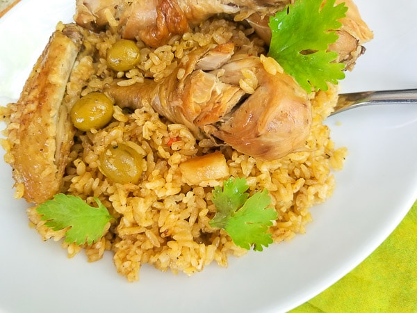 Puerto Rican Chicken and Rice (Arroz con Pollo) served on a white platter and topped with fresh cilantro.