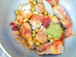 All other ingredients added to the chicken pieces cooking in the caldero (dutch oven).