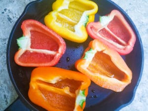 Tri-Color Bell Peppers cut in half in a cast iron skillet.