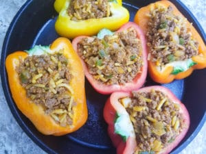 Peppers stuffed with the carne molida mix in a cast iron skillet.