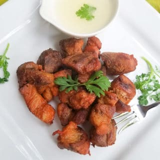 Delicious Carne Frita (Fried Pork Chunks) served with a side of garlic sauce on a white platter.