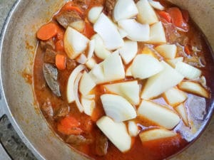 Potatoes and onions added to beef stew.