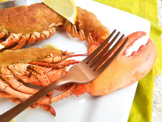Crispy Garlic Topping Baked Lobster (with Shrimp) on a white platter with lemon wedges.