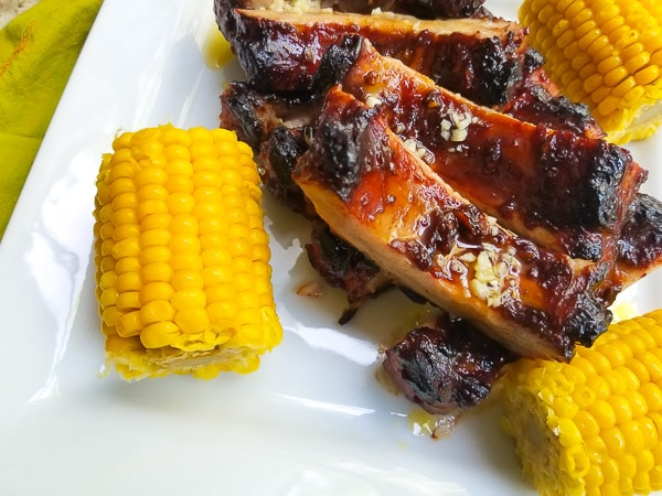 Hoison Garlic Baby Back Ribs with Corn on the Cob on a white platter.