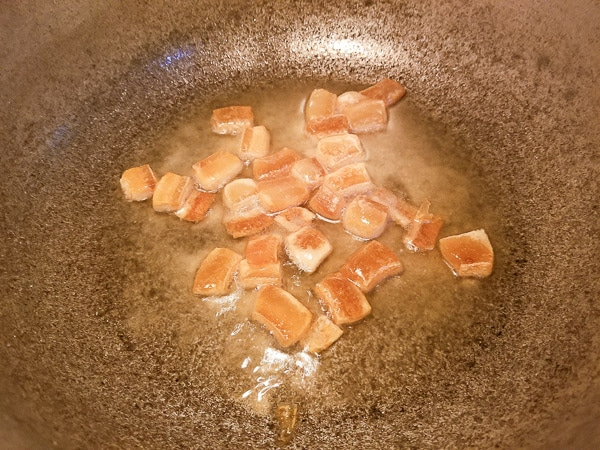 Tocino (pork fat) cooking in a caldero with oil for the Arroz Blanco.
