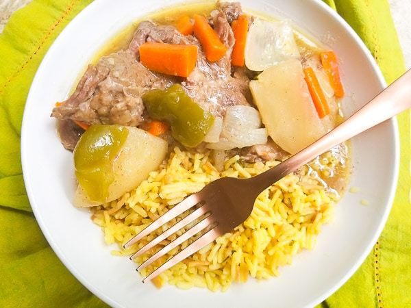Carne Mechada (Puerto Rican Style Pot Roast) served with yellow rice in a white bowl.