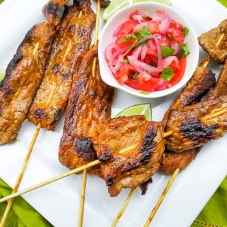 Chuzos de Carne served with curtido on a white platter.