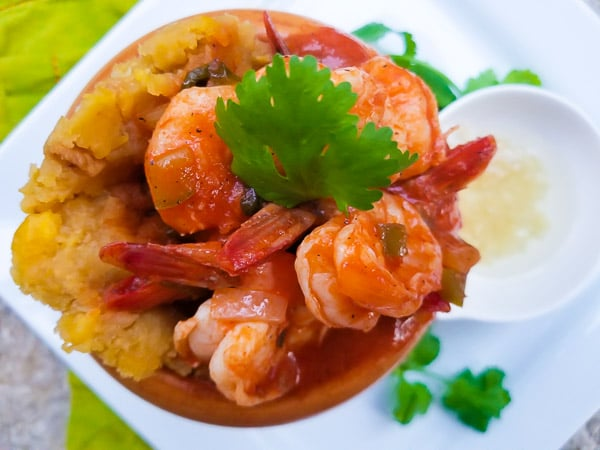 Mofongo con Camarones (Garlic Plantain Mash with Shrimp) served in a pilon (wooden mortar and pestle) and topped with salsa criolla.