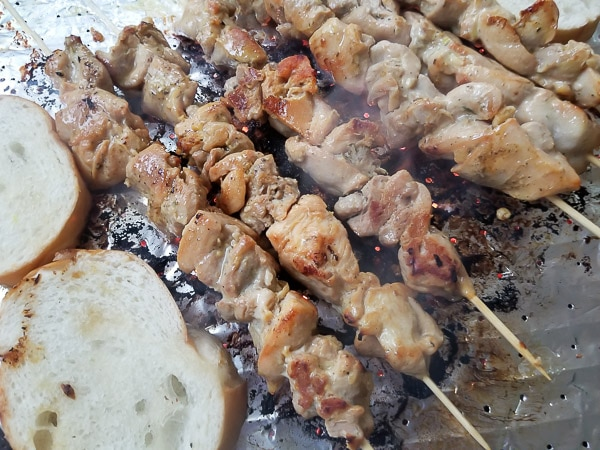 Chicken skewers and bread slices added beside chicken.