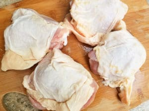Chicken thighs on a cutting board with skin and bone.