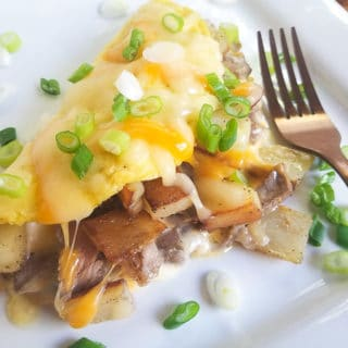 Steak Omelette with Potatoes topped with cheese and scallions. Served on a white platter.