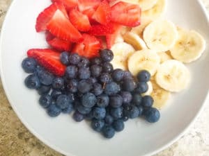 Strawberries, blueberries and bananas sliced and placed in a white bowl.