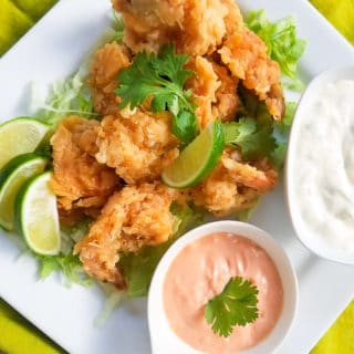 Camarones Empanizados (Battered Shrimp) served with jalapeno mayo sauce, mayo-ketchup with lime wedges on a white platter.