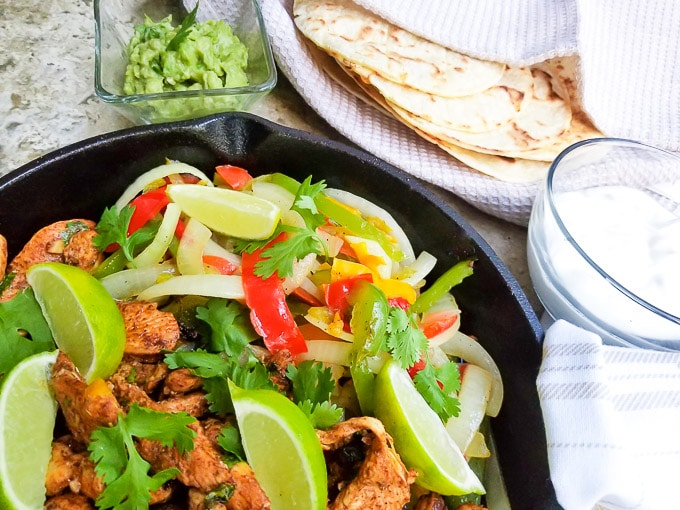 Fajitas de Pollo served with colored peppers and onions served in a skillet with a side of tortillas, guacamole and sour cream.