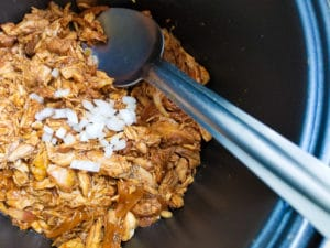 Instant Pot BBQ Chicken served in an instant pot, topped with chopped white onions.