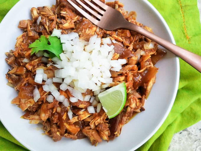 Instant Pot BBQ Chicken served in a white bowl, topped with chopped white onions.