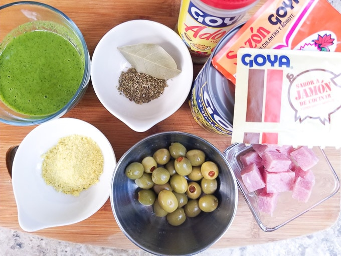 Ingredients to mak arroz con gandules displayed on top of a cutting board.