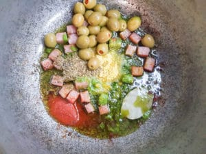 Sofrito and other ingredients added to pot for cooking base of rice dish.