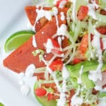 Enchiladas Potosinas served and topped with shredded lettuce, avocados, tomatoes and Mexican cream on a white platter.