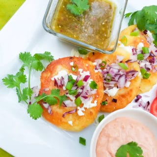 Tortitas de Papa (Potato Fritters) served on a white plate with salsa verde and mayo ketchup.