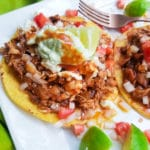 BBQ Chicken Tostadas topped with avocado/sour cream, chopped tomatoes, chopped onions and lime wedges.