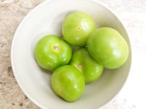 De-husked and rinsed tomatillos in a white bowl.
