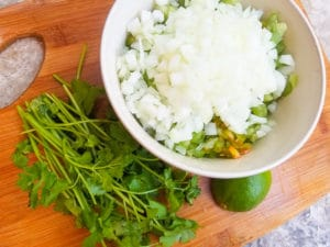 Ingredients to make tomatillo pico de gallo on a wood cutting board.