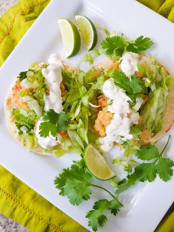 Tostadas de Camaron topped with shredded lettuce, jalapeno tartar sauce, tomatillo pico de gallo and cilantro, served on a white platter with lime wedges.