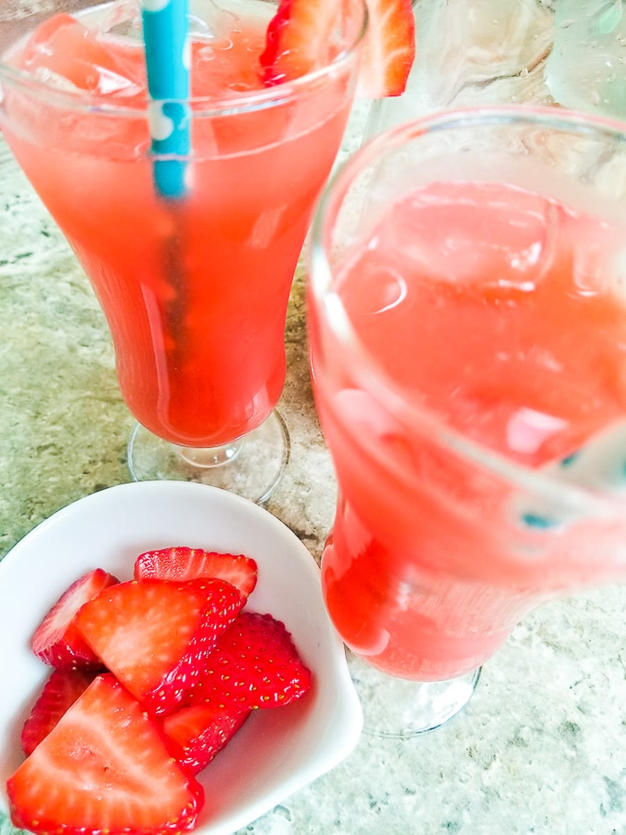 Agua de Fresa (Mexican Strawberry Water) served in clear glasses with ice and blue striped straws and a small side of fresh strawberries served in a small white bowl.