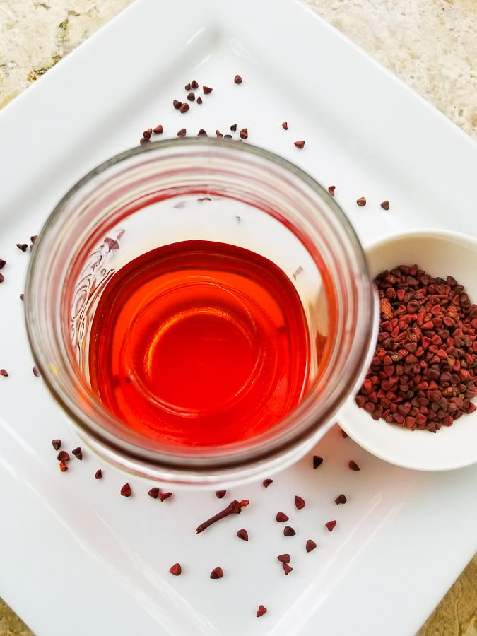 Annatto oil (achoite oil) stored in a Mason jar and photographed on top of a white plate with annatto (achiote) seeds right beside it.