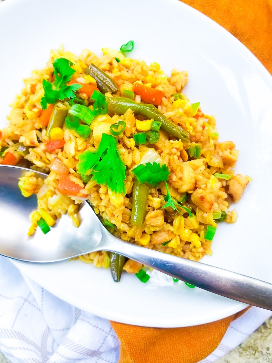 Arroz Chino (Chinese Fried Rice with Chicken) served in a white oval platter, topped with cilantro sprigs and a large white spoon for serving.